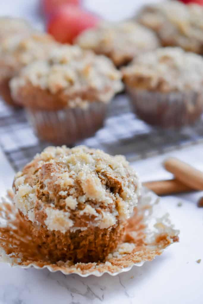 Apple streusel muffins with more muffins on a cooling rack behind them