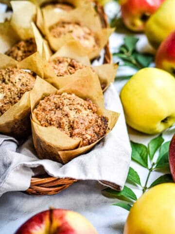 A close up of one of the apple streusel sourdough muffin surrounded by apples