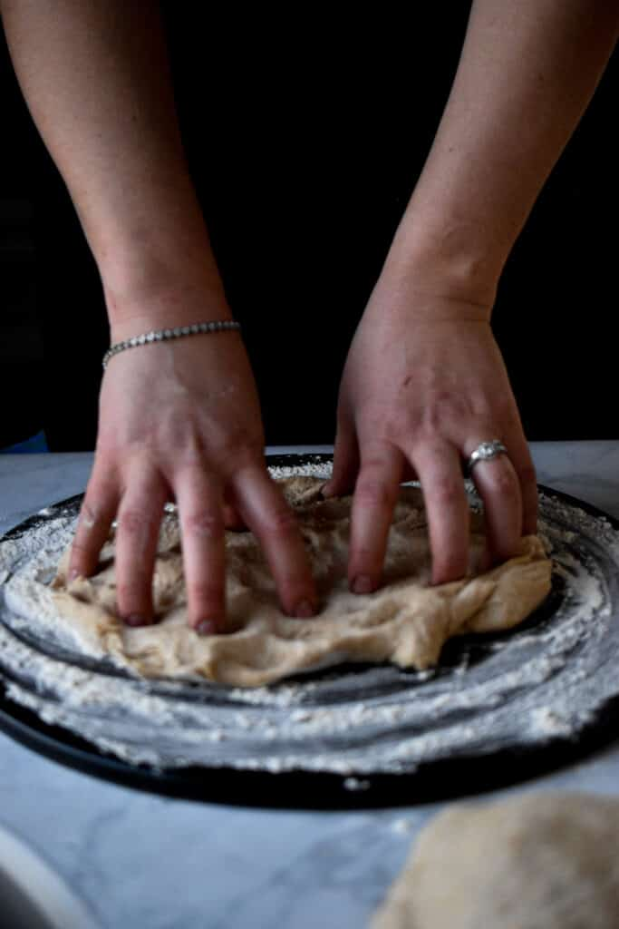 spreading the cheese on the pizza dough