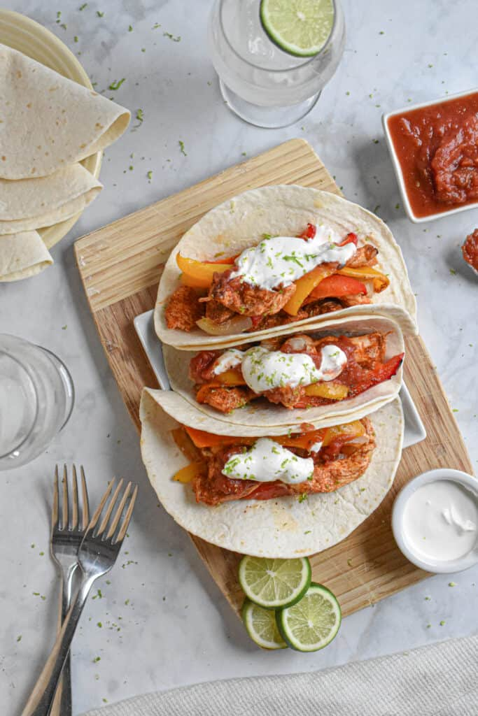 Easy Sheet Pan Chicken Fajitas served with sour cream and salsa