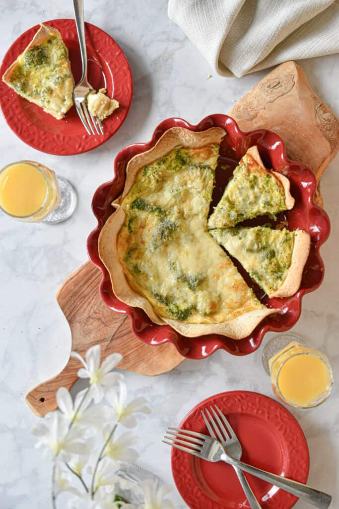 broccoli cheddar quiche with tortilla crust laid out in a brunch spread