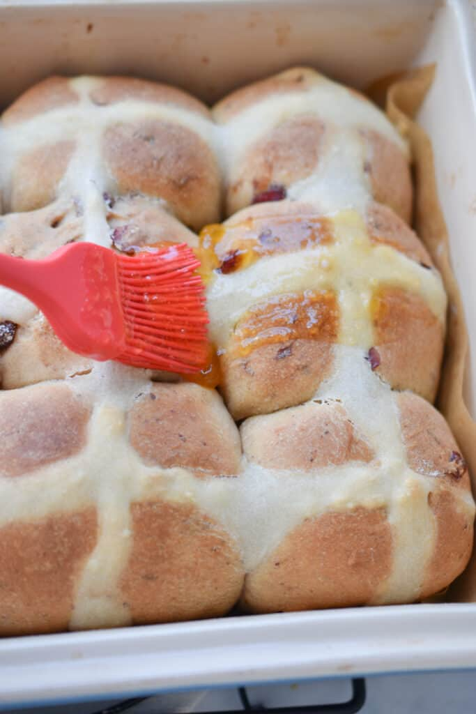 After the cinnamon hot cross buns are out of the oven, brush with the apricot glaze