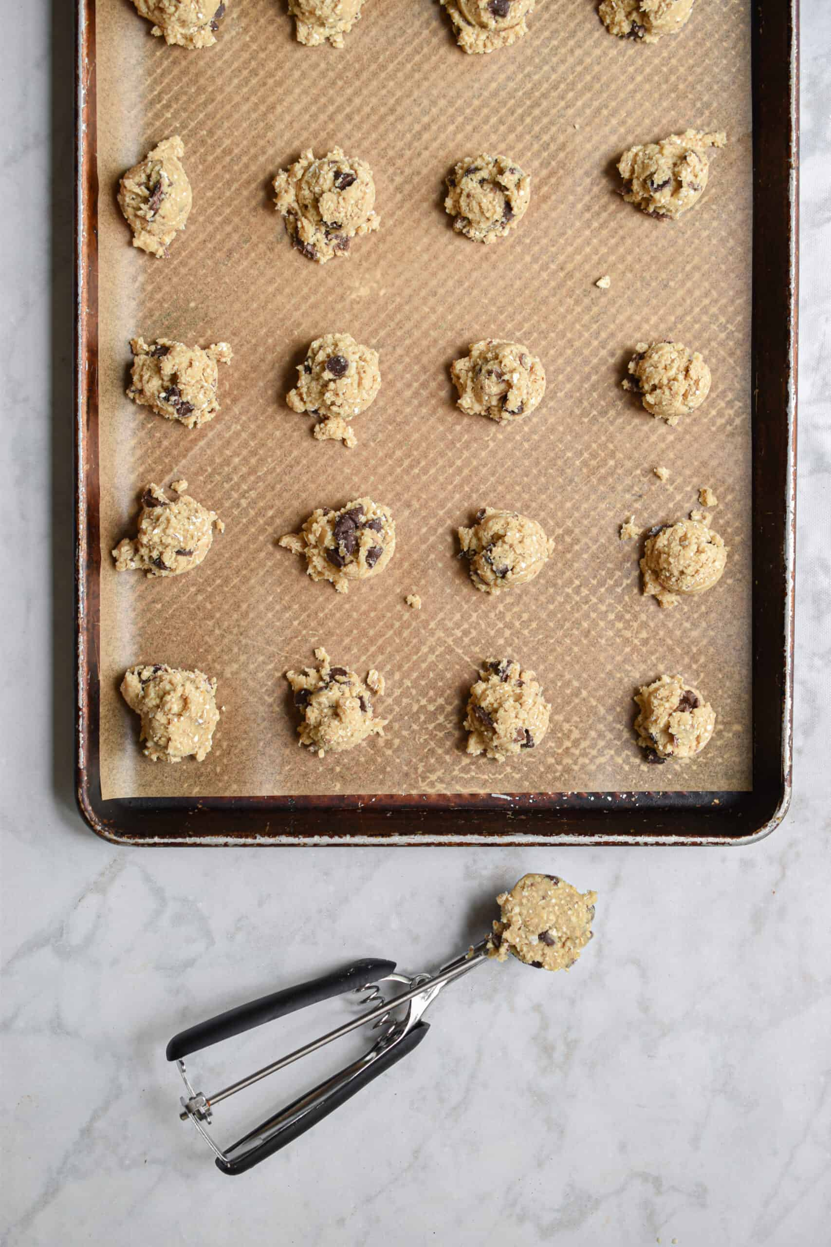Dough of the double chocolate oat cookies laid out on a sheet pan with one cookie still in the cookie scoop