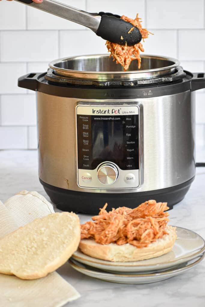 Instant Pot Pulled BBQ Chicken being removed from the Instant Pot