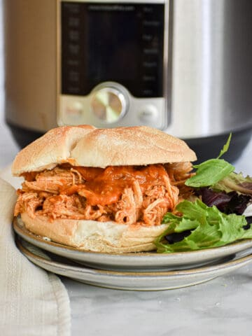 Pulled Chicken Sandwich in from of the Instant Pot with a salad on the side