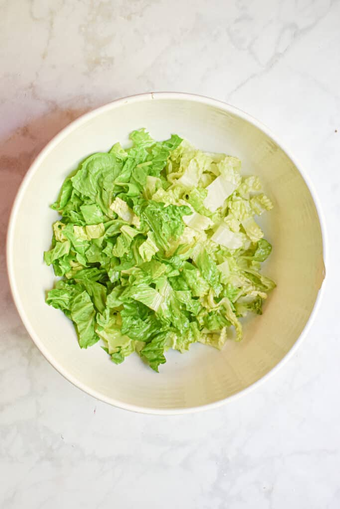 Add the romaine lettuce to a large bowl