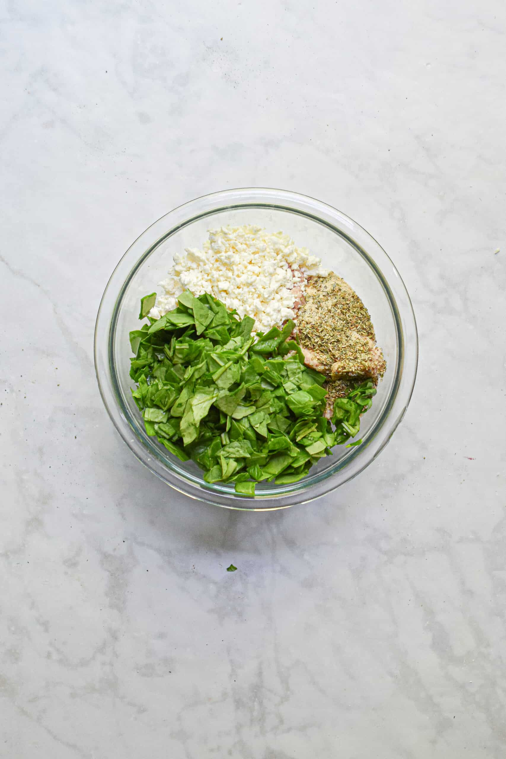Add the spinach to the bowl of feta, seasonings, and ground chicken