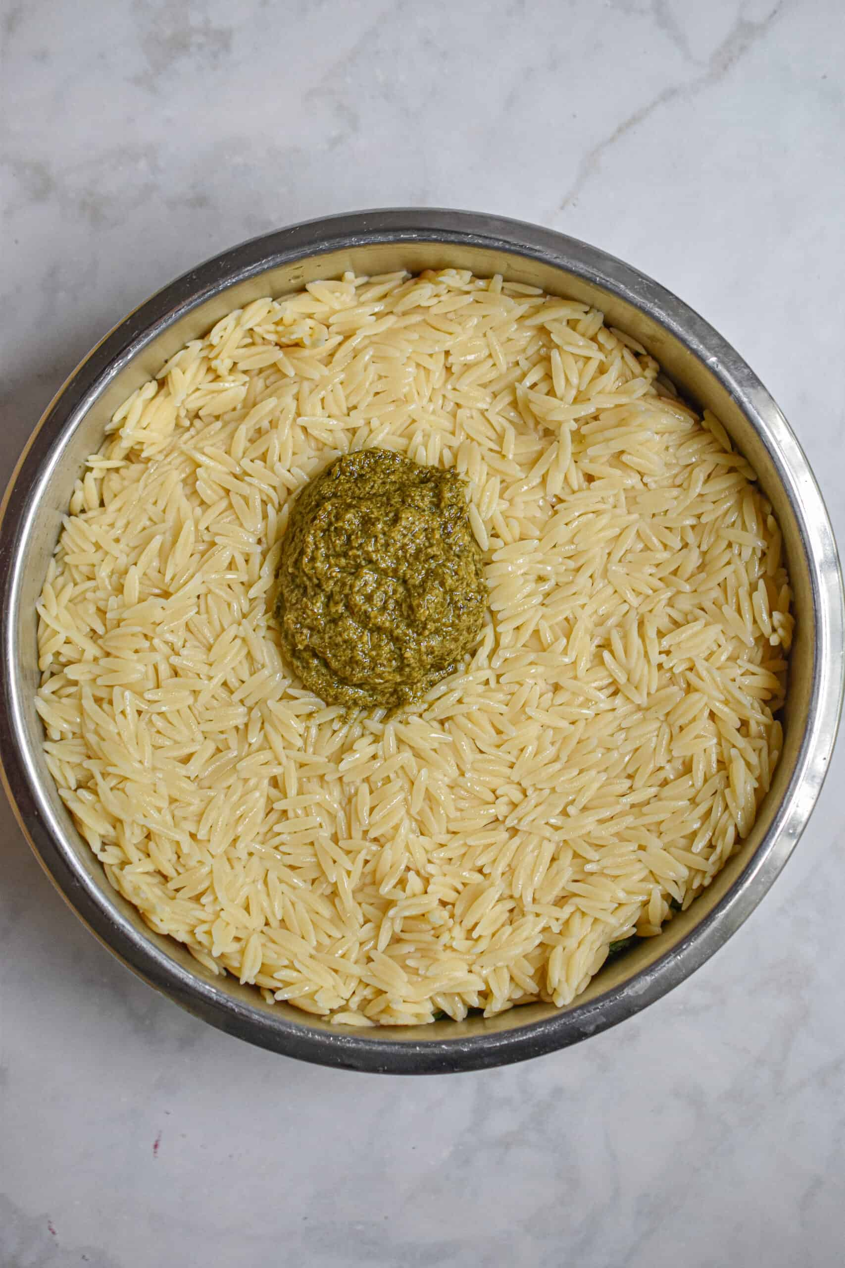 Add the orzo and pesto to the bowl