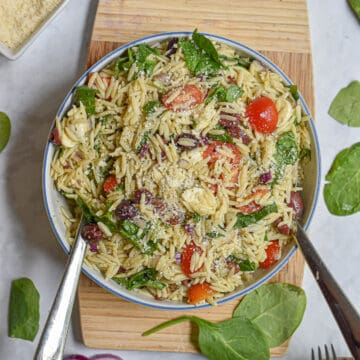 Orzo Pesto Pasta salad on a wooden cutting board