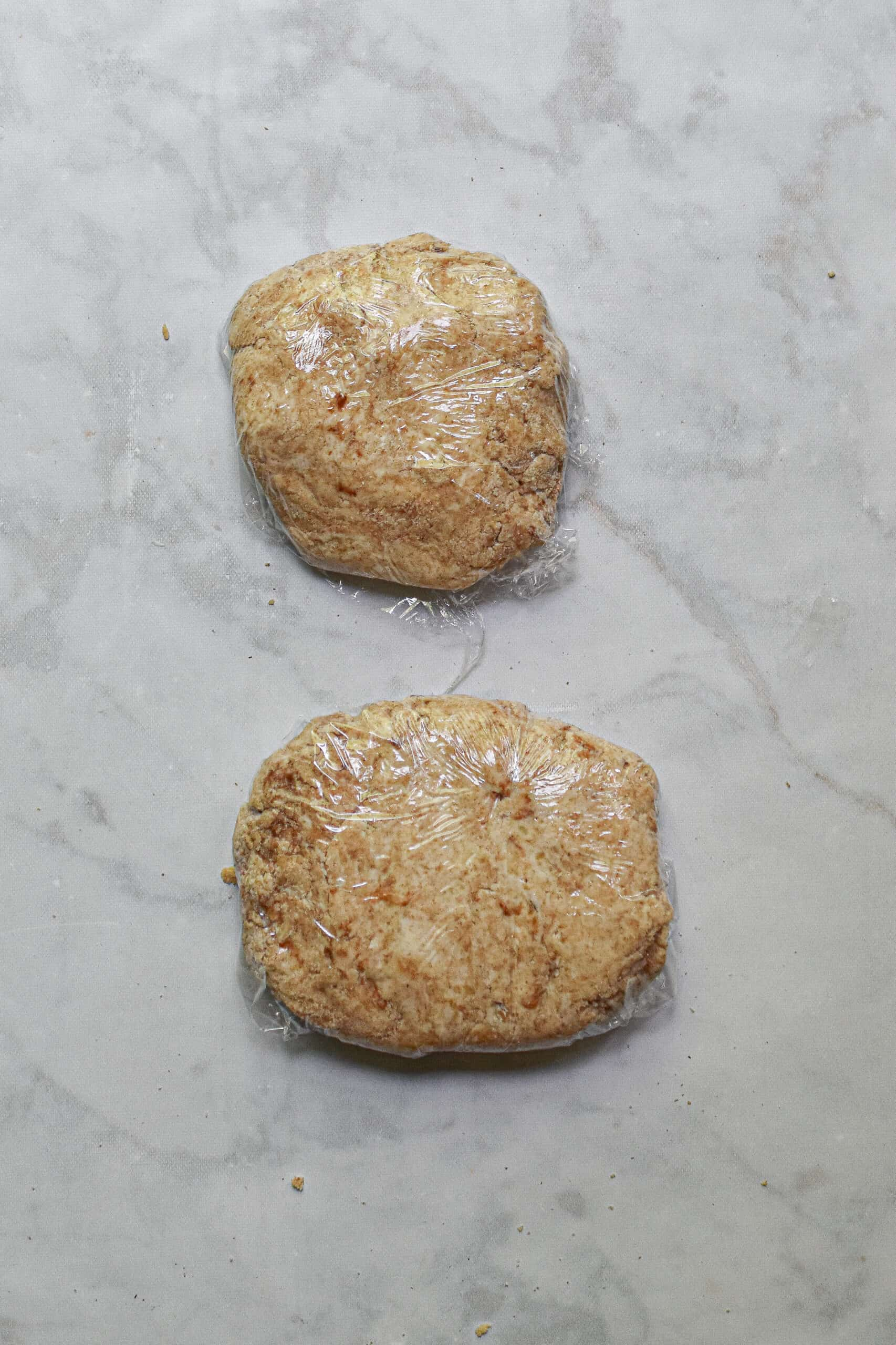 two discs of dough, wrapped individually and ready to be placed in the refrigerator