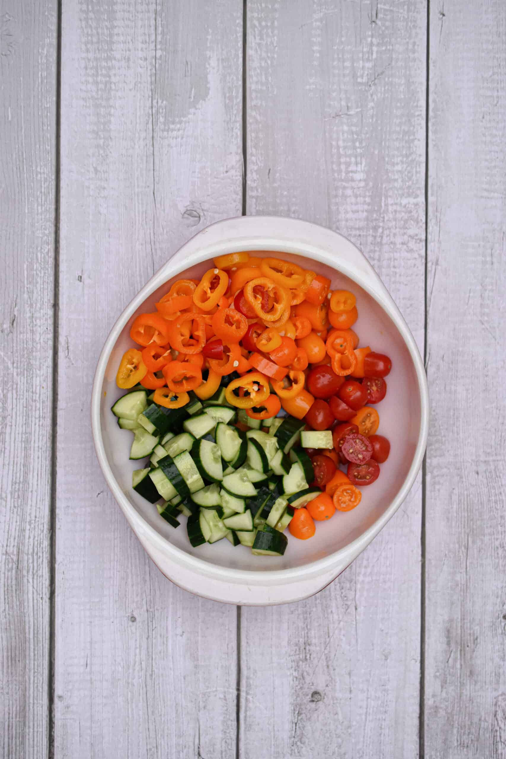 the cut up cucumbers, peppers, and cherry tomatoes are in a bowl