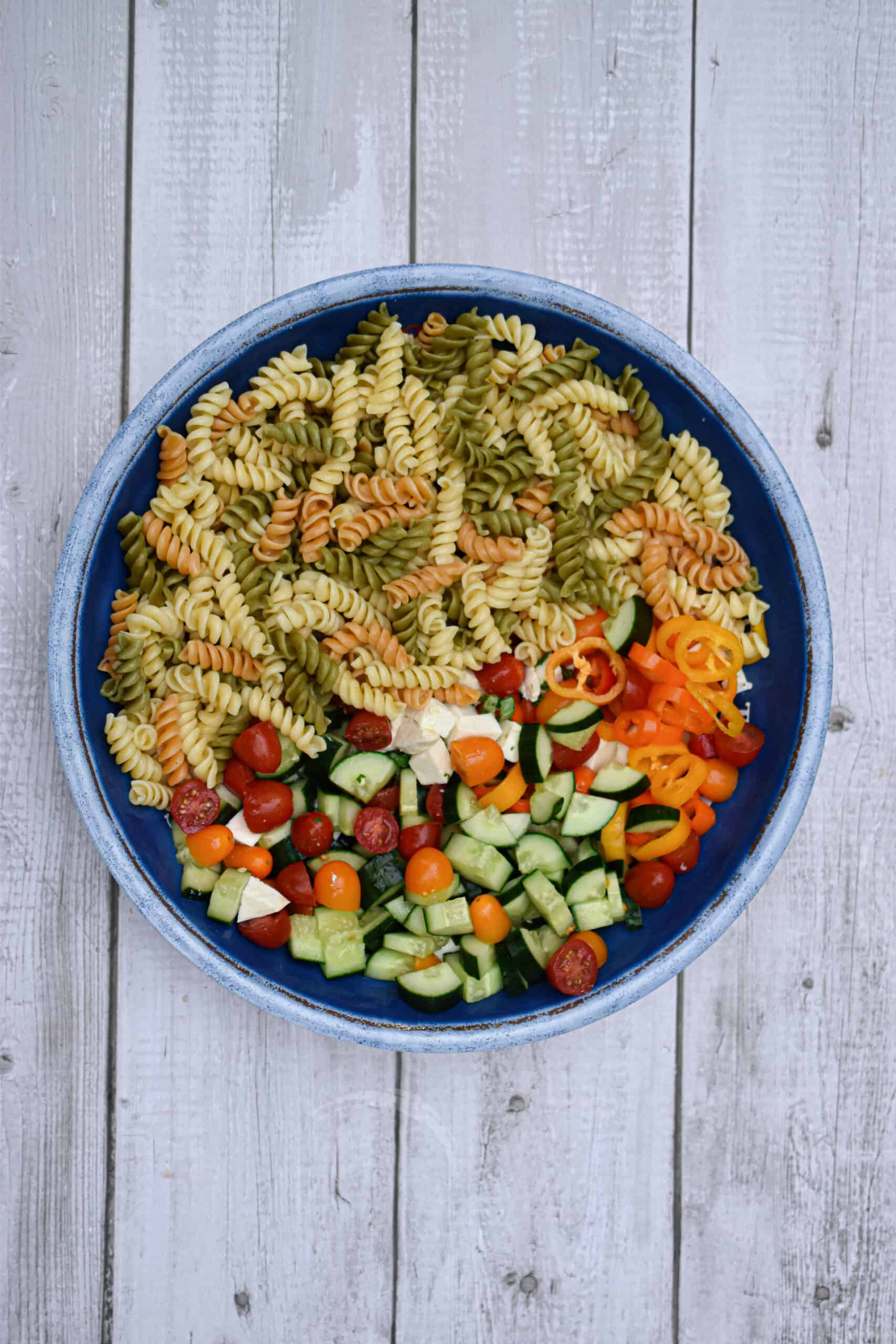 The pasta is add to the bowl for the garden vegetable and herb pasta salad