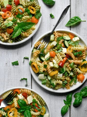 garden vegetable and herb pasta salad on three plates surrounded by fresh basil