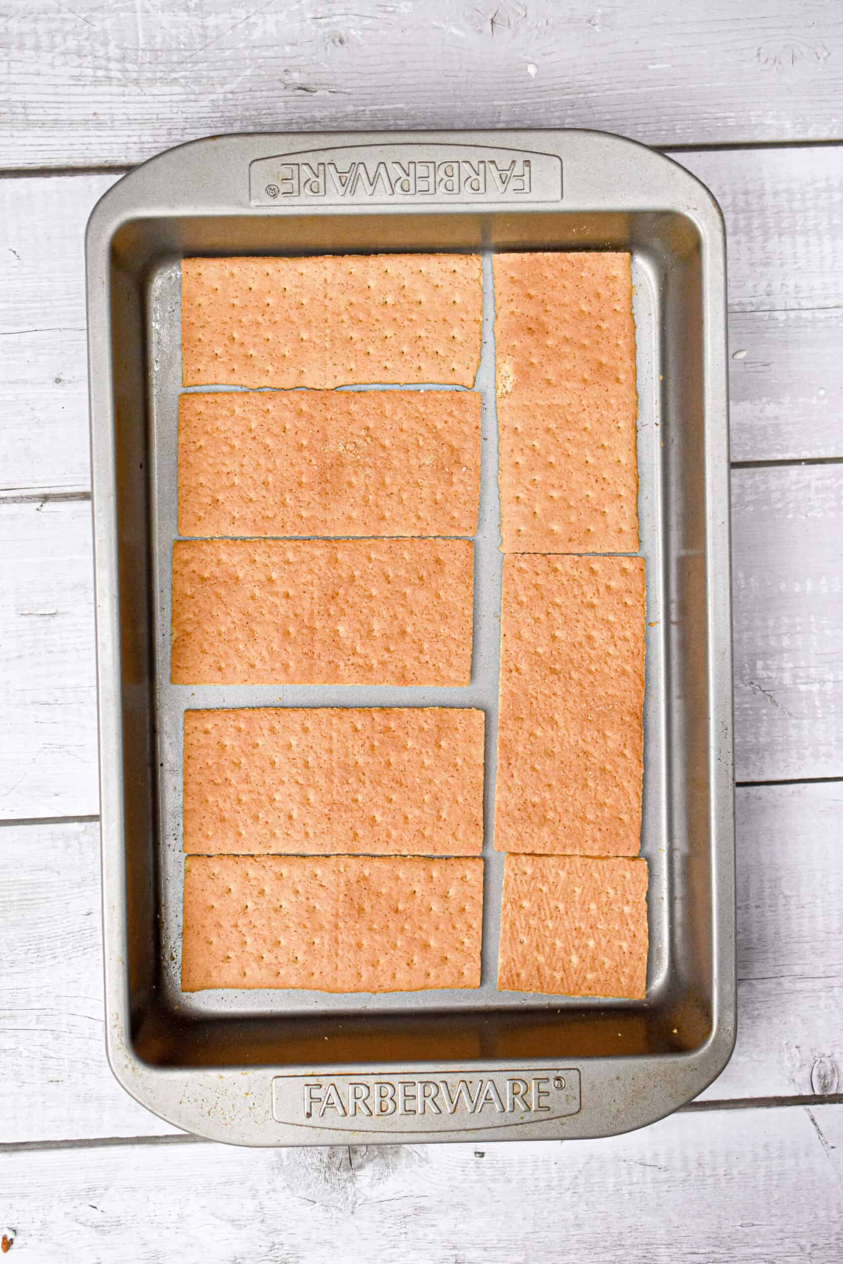 The red white and blue icebox cake is started by adding graham crackers to a large pan