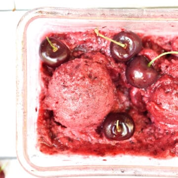A scoop of the cherry vanilla sorbet surrounded by cherries