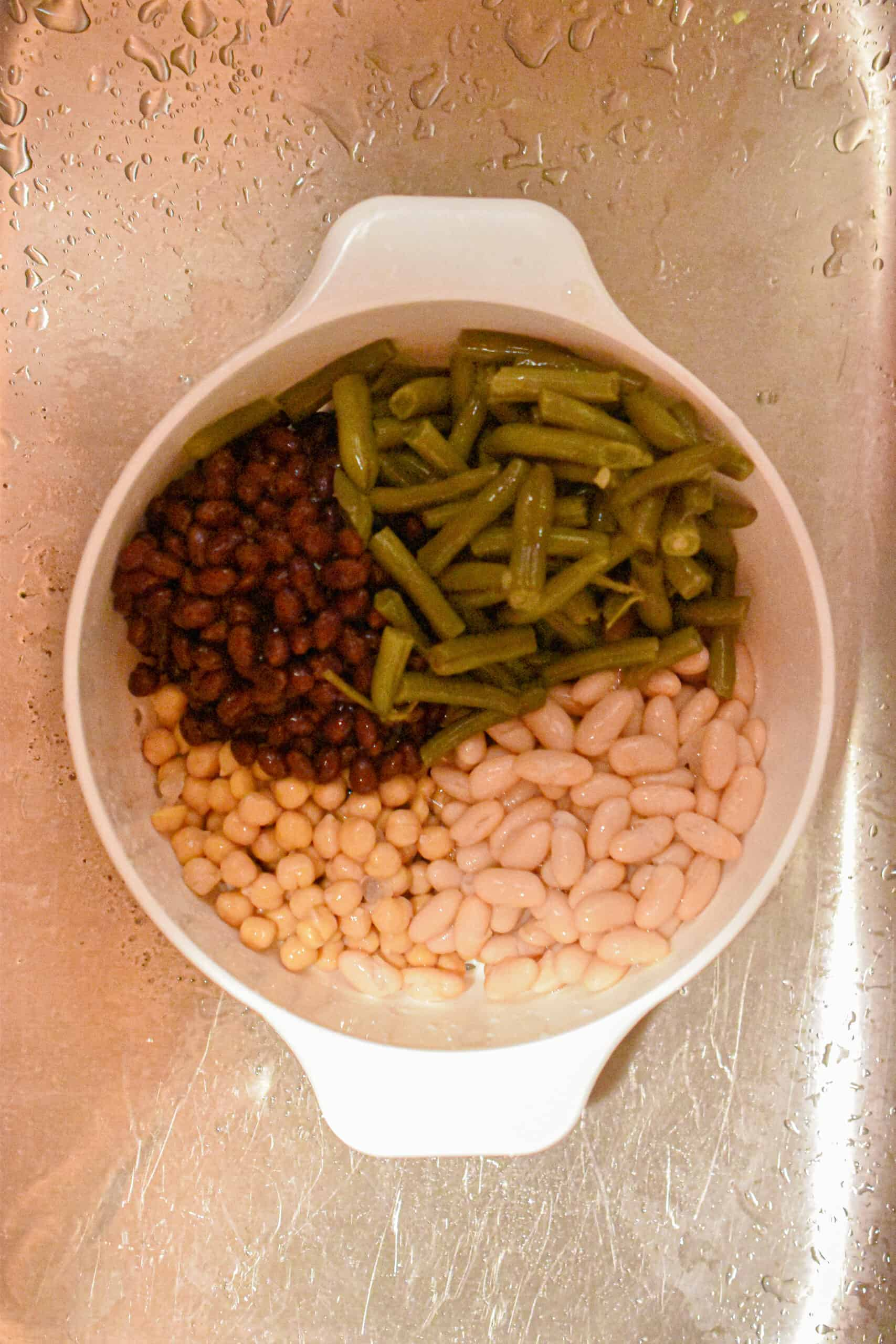 The cans of beans are washed and drained in a colander