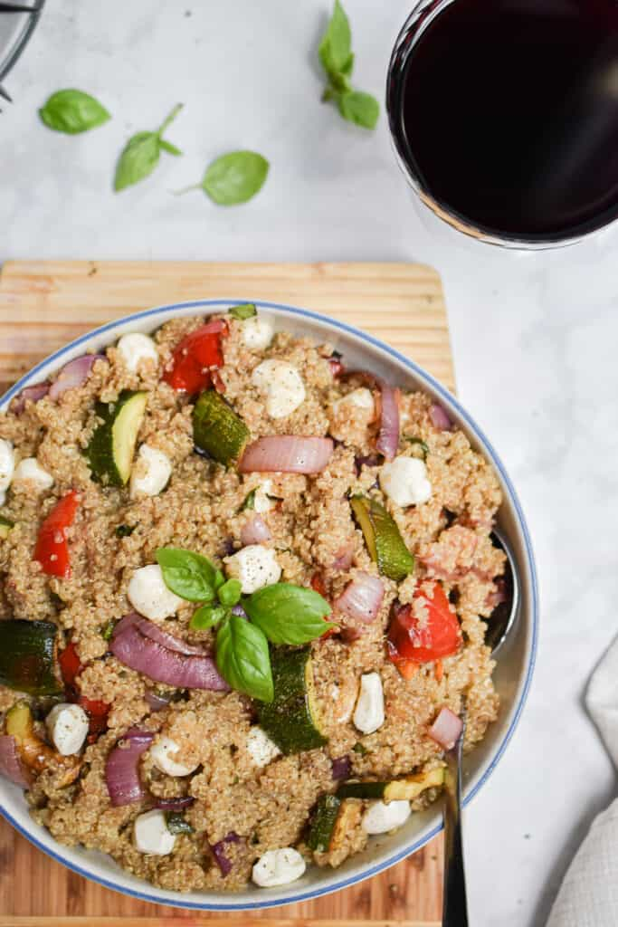 an overhead shot of the grilled vegetable quinoa salad with a glass of wine