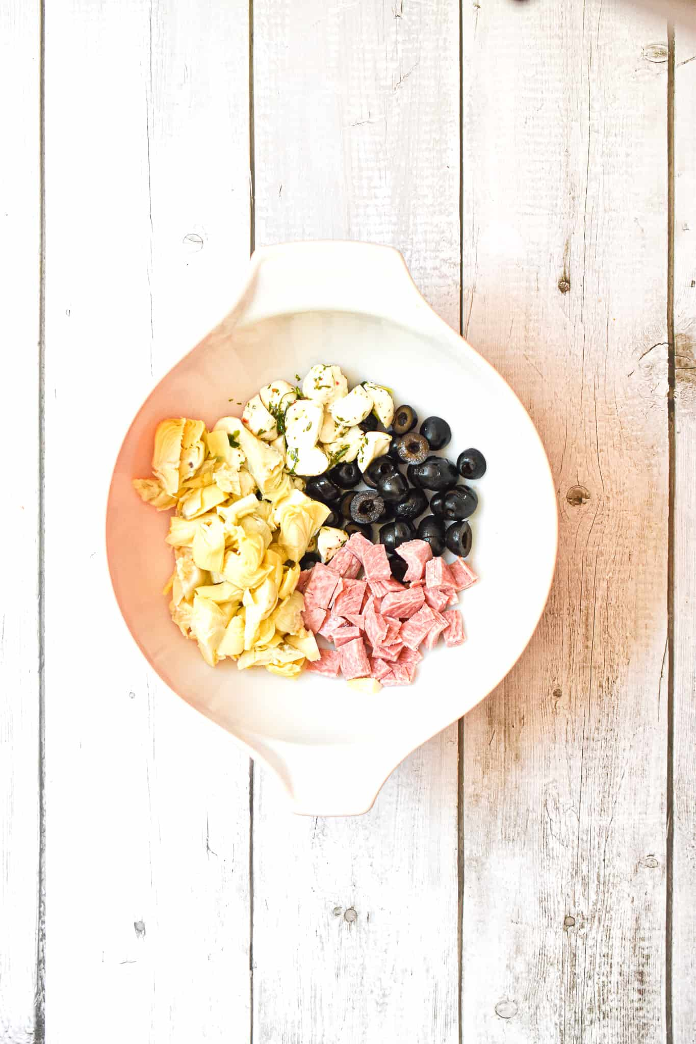 The black olives, marinated mozzarella, salami, and chopped artichokes are in a bowl