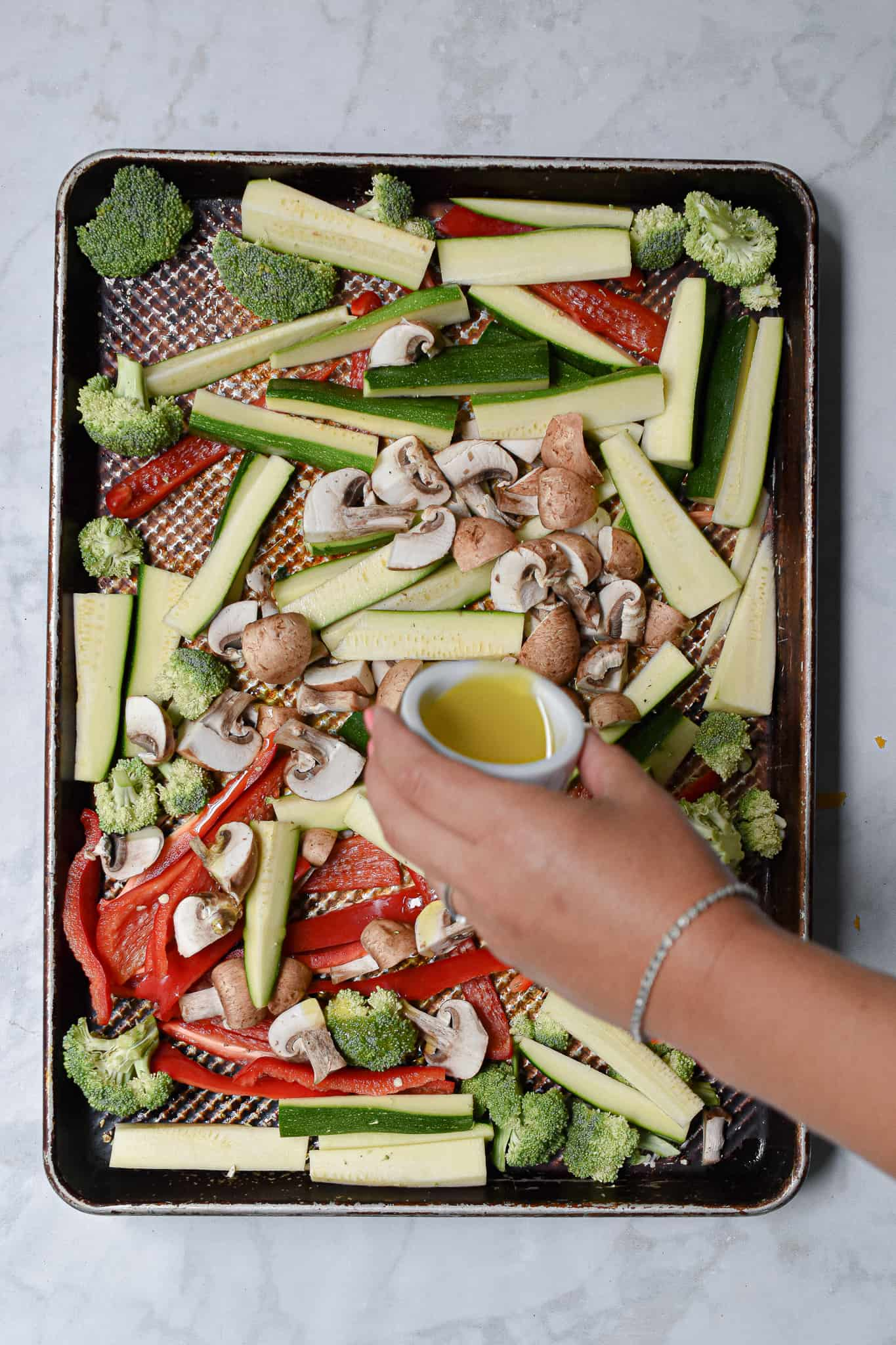 The olive oil is being poured over the cut up vegetables