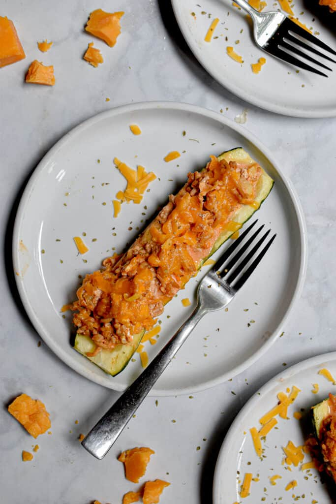 One half of a zucchini is on a plate with a fork
