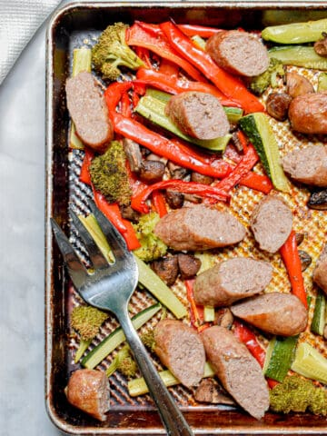 The sheet pan brats with roasted vegetables with a serving fork