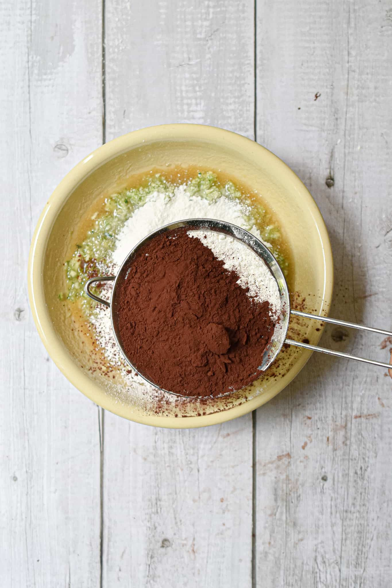 The dry ingredients are sifted into the death by chocolate zucchini bread mixture