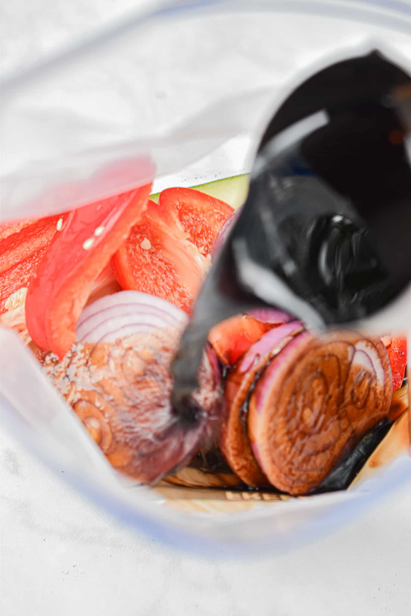 The balsamic vinegar is poured into the bag with the vegetables