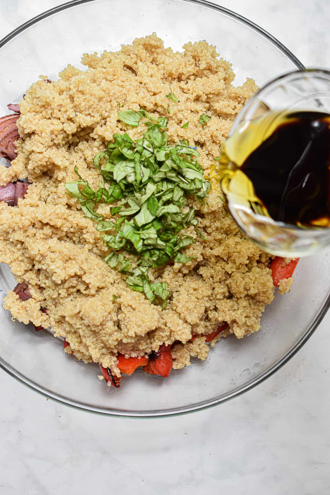 the vinaigrette is poured on top of the quinoa grilled vegetable salad