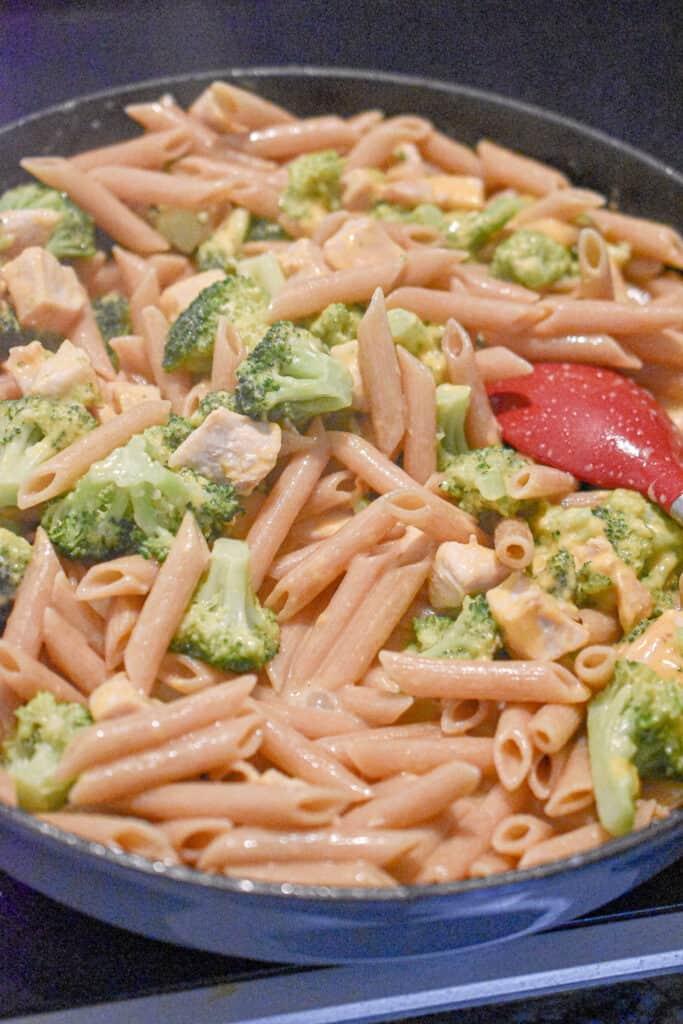 The one pot broccoli chicken pasta is stirred to combine.