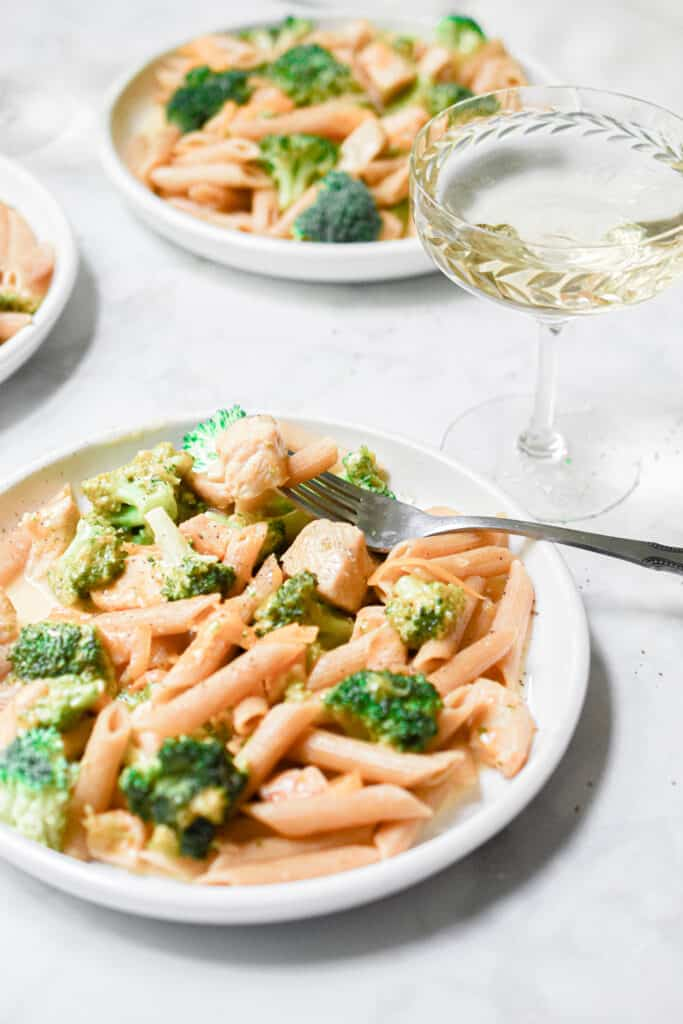 Two plates of the pasta with a glass of wine.