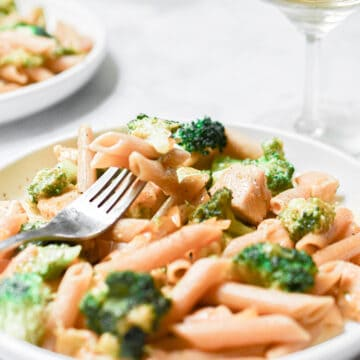 Some of the one pot chicken broccoli pasta is on a fork laying on the plate.
