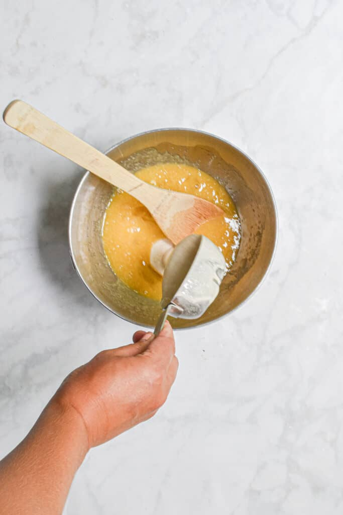 The sourdough discard is added to the bowl with the eggs and sugar.