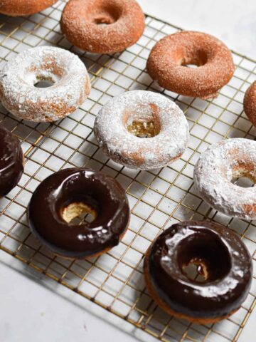 A close up of the sourdough doughnuts, some covered in cinnamon sugar, some covered in chocolate icing, some covered in powdered sugar