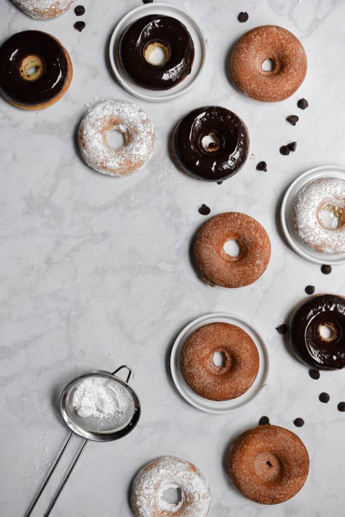 An overhead shot of the baked sourdough doughnuts spread out on the left side of the shot.