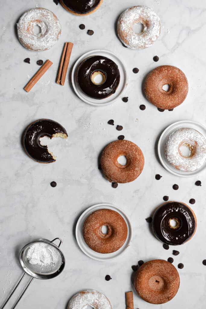 An overhead shot of the doughnuts and one chocolate doughnuts has a bite taken out of it.