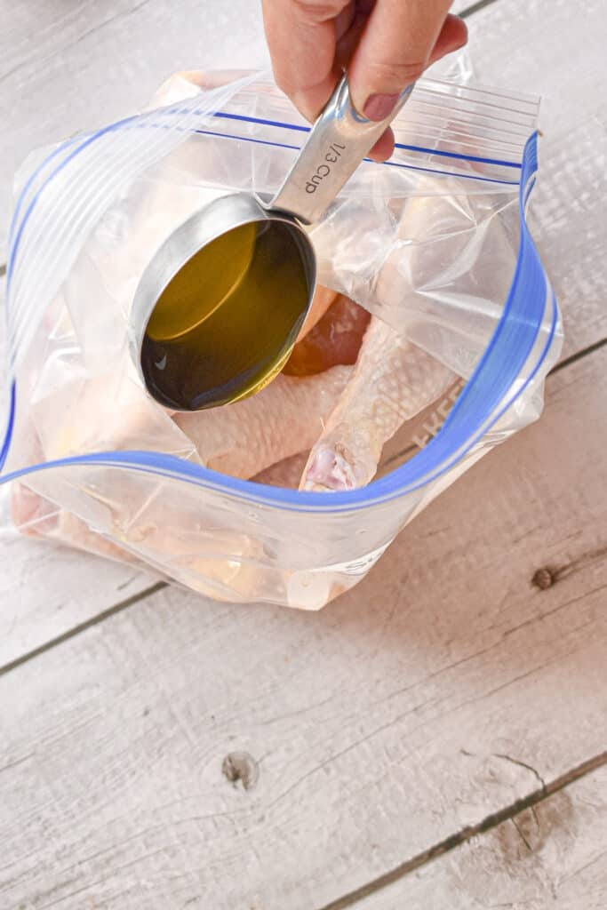 The olive oil and vinegar are added to the chicken drumsticks