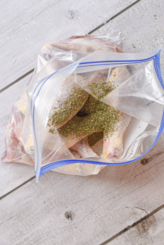 Italian seasoning is added to the Ziploc bag of drumsticks