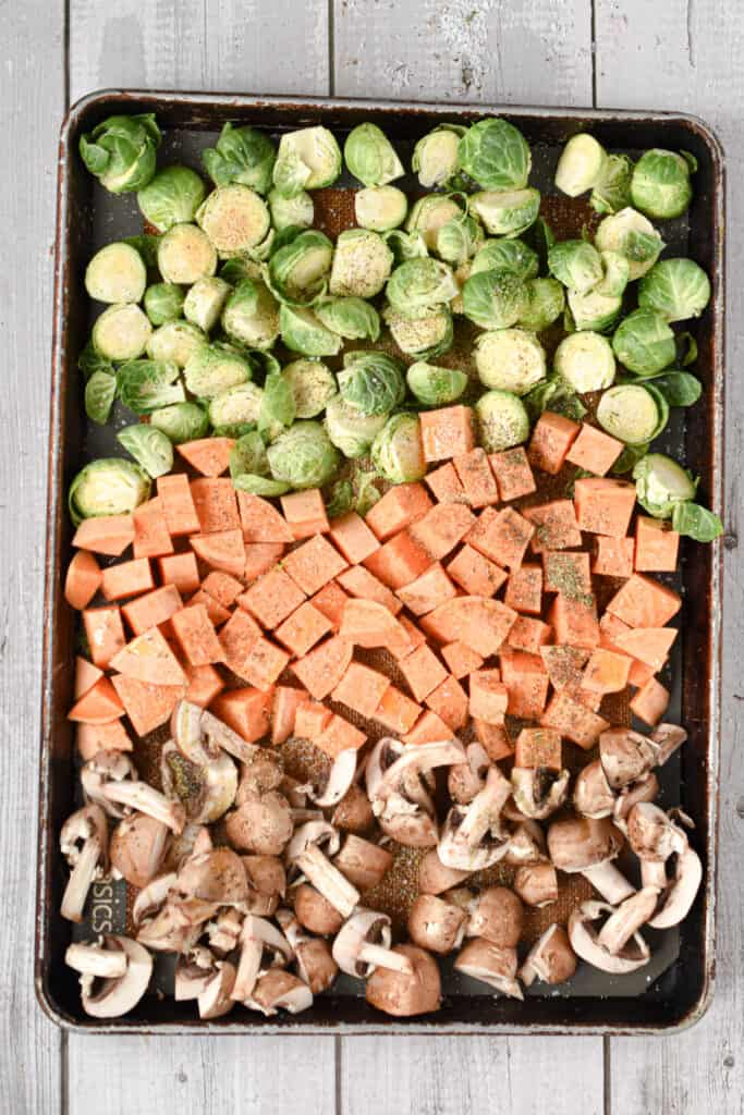 The vegetables are laid out on a sheet pan and topped with granulated garlic, olive oil, and seaosnings
