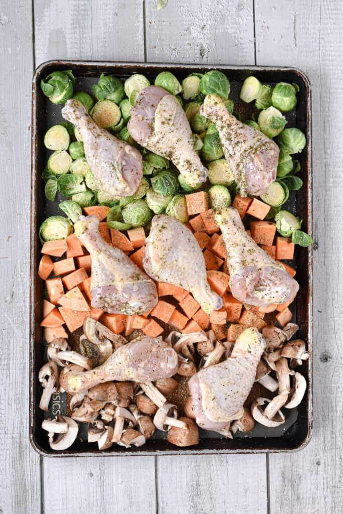 The drumsticks are laid out on top of the chopped vegetables