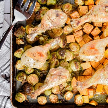 The chicken drumstick sheet pan dinner is laid out with a serving fork on the sheet pan