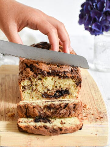 A knife is cutting into the nutella zucchini bread
