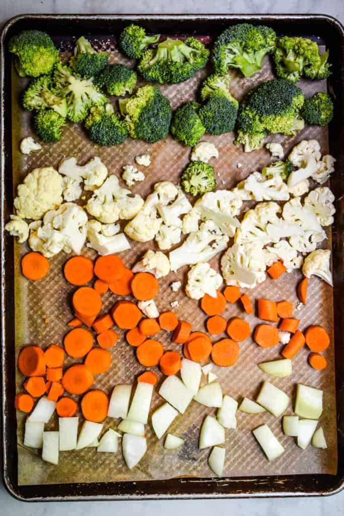 An overhead view of the cut vegetables on a sheet pan