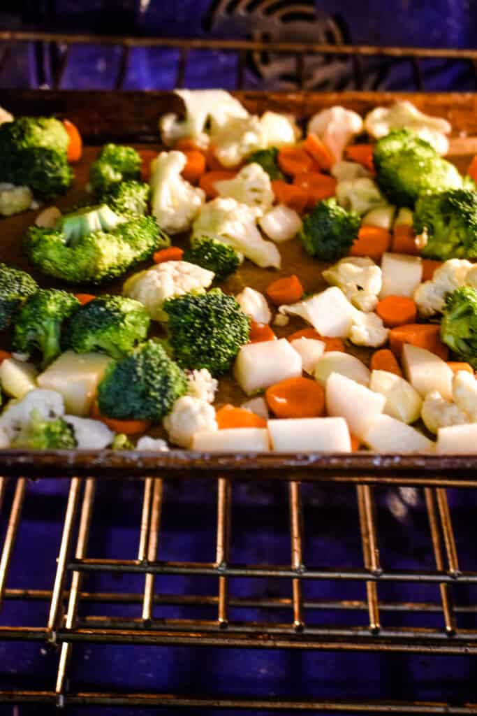 The sheet pan with the vegetables are in the oven