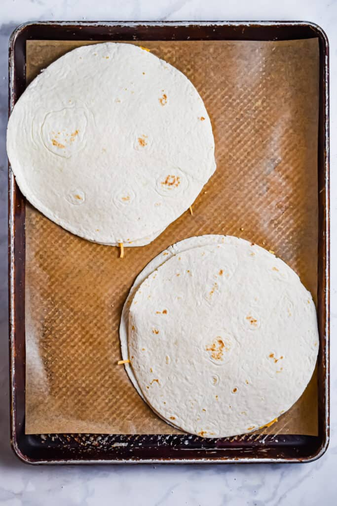 The chicken and cheese is topped with another tortilla for the buffalo chicken sheet pan quesadillas