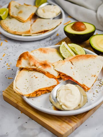 The quesadillas are served with avocado and sour cream