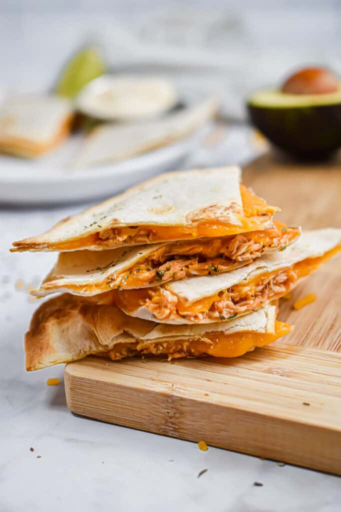 The buffalo chicken sheet pan quesadillas are stacked on top of a wooden cutting board.