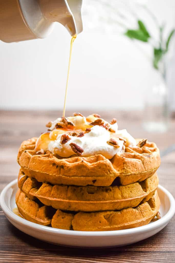 Syrup is being poured over the sourdough pumpkin waffles
