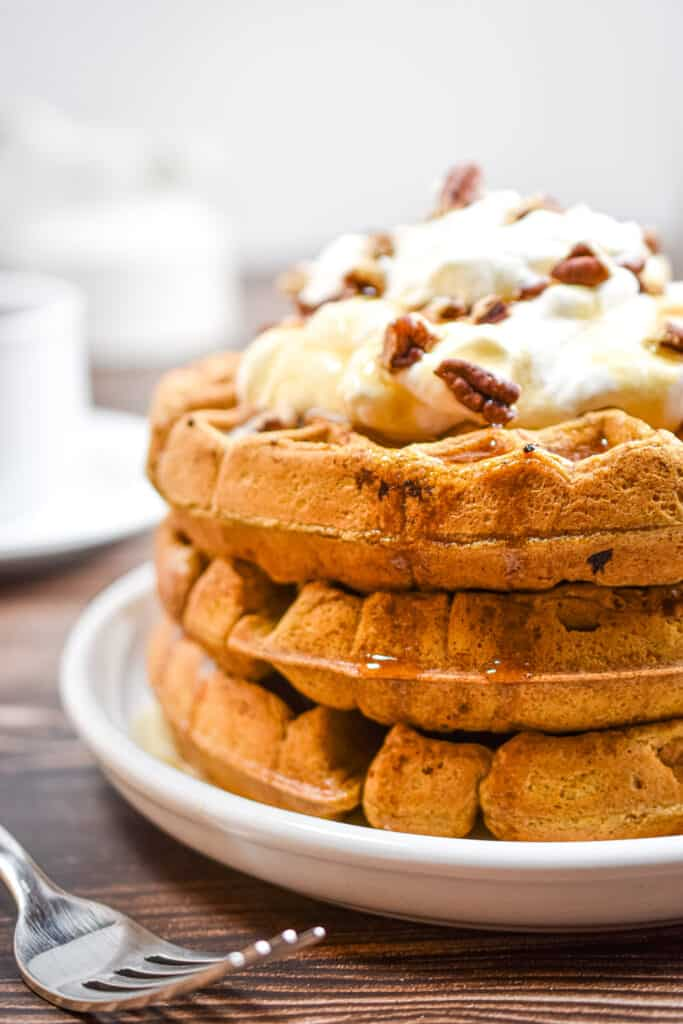 The Sourdough pumpkin waffles are stacked three high with whipped cream on top