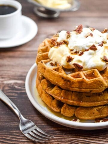 A stack of sourdough pumpkin pancakes is topped with whipped cream and pecans