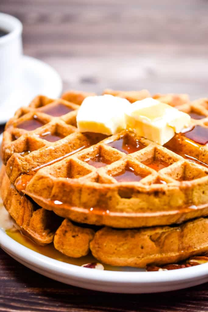 The waffles are topped with two pats of butter